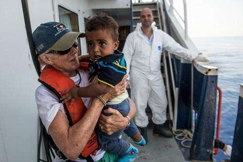 Alison Criado-Perez, medical team leader on the MY Phoenix search and rescue vessel, carries 9-month-old Isrom from Eritrea.