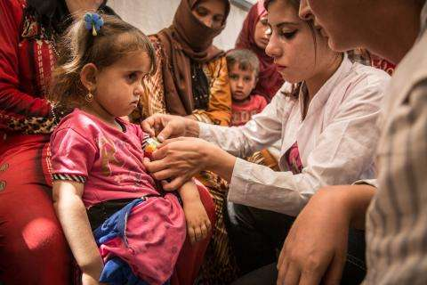 MSF health worker tends to a young girl at a camp in Syria